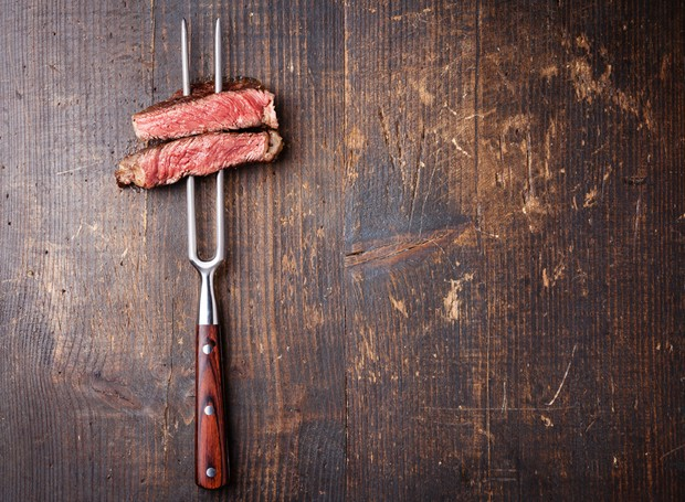 Slices of beef steak on meat fork on dark wooden background (Foto: Getty Images/iStockphoto)
