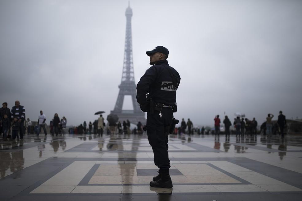 Policial patrulha praça Trocadero, em frente à Torre  Eiffel, neste sábado (6) em Paris (Foto: AP Photo/Kamil Zihnioglu)