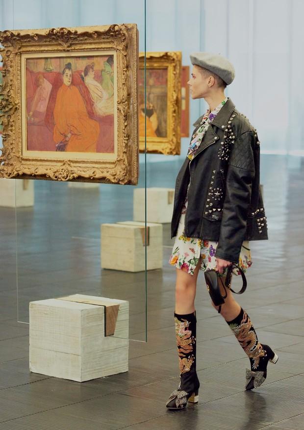 Michi posa ao lado de O Divã (1893) com jaqueta (R$ 35.840), vestido (R$ 8.690), pochete (R$ 4.140), boina (R$ 1.240) e bota (R$ 8.690), tudo Gucci (Foto: Hick Duarte)