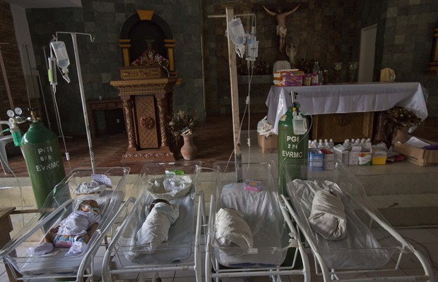 Bebês doentes e prematuros em berços na capela de um centro médico em Tacloban, nas Filipinas. O lugar foi ocupado pelos leitos das crianças após a área originalmente destinada a eles ter sido destruída pelo tufão Haiyan (Foto: David Guttenfelder/AP)