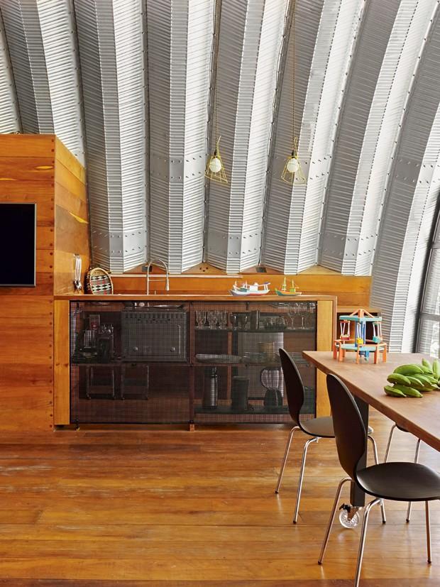 Sala de jantar | O balcão de madeira com tela metálica separa a cozinha equipada com eletrodomésticos de inox e pendentes da Tok&Stok (Foto: Victor Affaro)