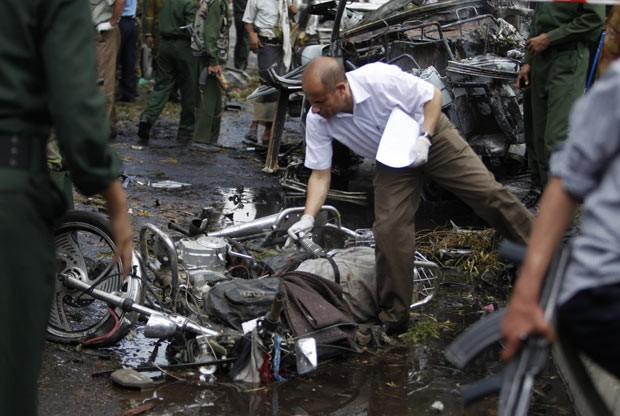 Perito observa destroços após explosão de bomba nesta terça-feira (11) em Sanaa, capital do Iêmen (Foto: AP)
