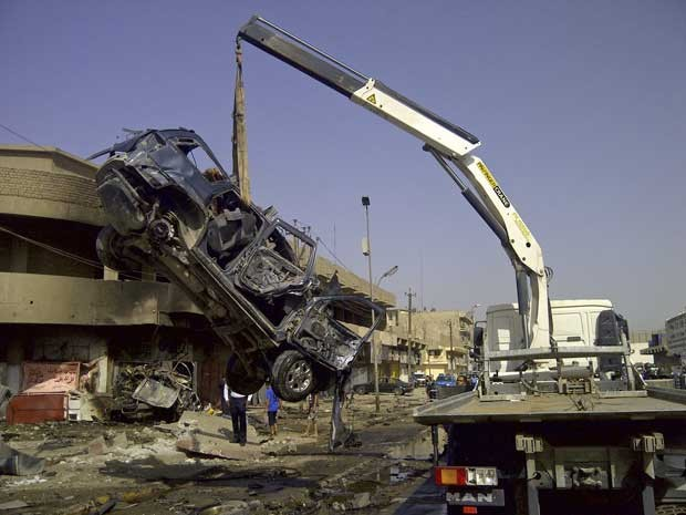 Um veículo destruído é removido do local de um atentado em Bagdá que matou peregrinos xiitas que estavam a caminho de um festival religioso. (Foto: Saad Shalash / Reuters)