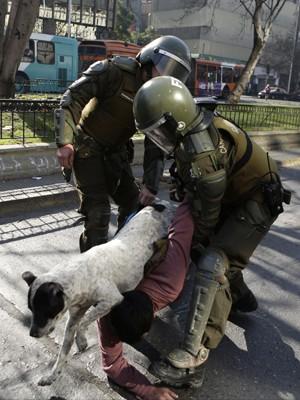 Cão pula sobre homem que está sendo detido pela polícia em manifestação de professores, em Santiago, na quarta (17) (Foto: AP Photo/Jorge Saenz)