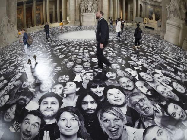 Pessoas visitam a exposição 'Au Pantheon!' do artista francês JR, em Paris. O projeto Inside Out composto de milhares de rostos de parisienses foi escolhido para cobrir o chão e o teto do edifício em Paris (Foto: Martin Bureau/AFP)
