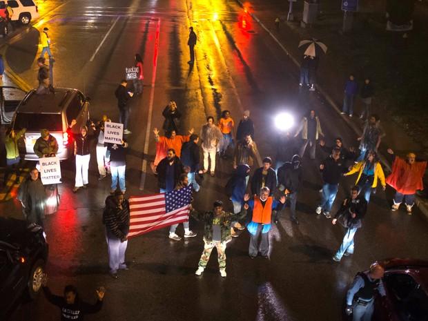 Manifestantes, exigindo a condenação de um policial branco que matou a tiros um adolescente negro desarmado em agosto, param o trânsito durante uma marcha em um subúrbio de St. Louis, Missouri, nos Estados Unidos (Foto: Adrees Latif/Reuters)