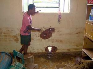 Rapaz mostra buracos abertos na parede da casa em São Pedro para água da chuva sair (Foto: Reprodução/EPTV)