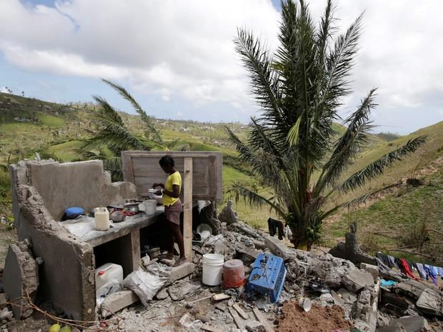 Uma mulher prepara comida na cozinha de sua casa destruída pelo furacão Matthew nos arredores de Port Salut, no Haiti (Foto: Andres Martinez Casares/Reuters)