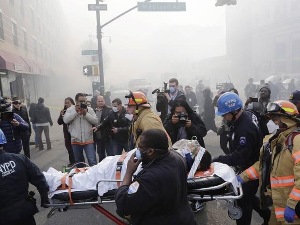 Pessoa ferida recebe socorros após ser retirada dos destroços do desabamento no Harlem, em NY (Foto: Mark Lennihan/AP)