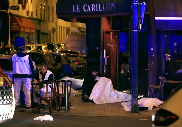 Corpos no chão em frente a restaurante em Paris  (Foto: Thibault Camus/AP)