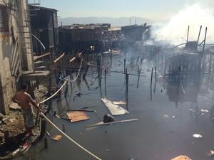 Moradores utilizam água da maré para combater as chamas (Foto: Orion Pires/G1)