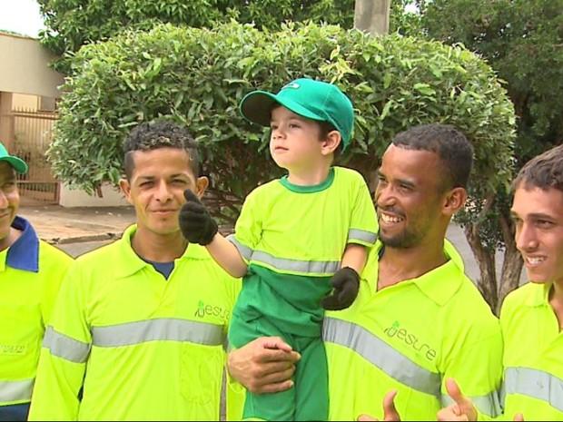 Miguel vibra com a equipe da coleta de lixo na rua onde mora na zona leste de Ribeirão Preto (Foto: Ronaldo Gomes/EPTV)