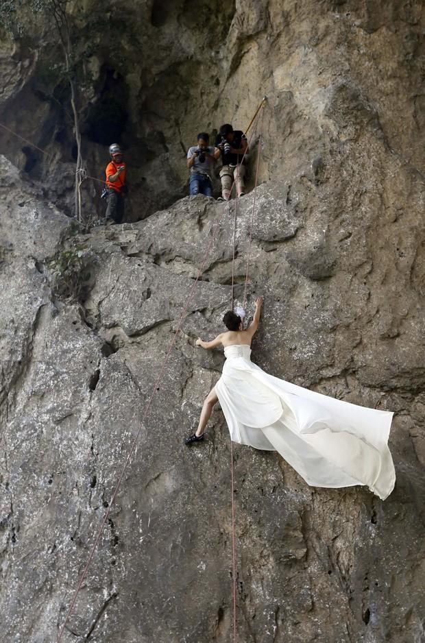 Casal posa para fotos de casamento durante escalada na China (Foto: Reuters/Stringer)