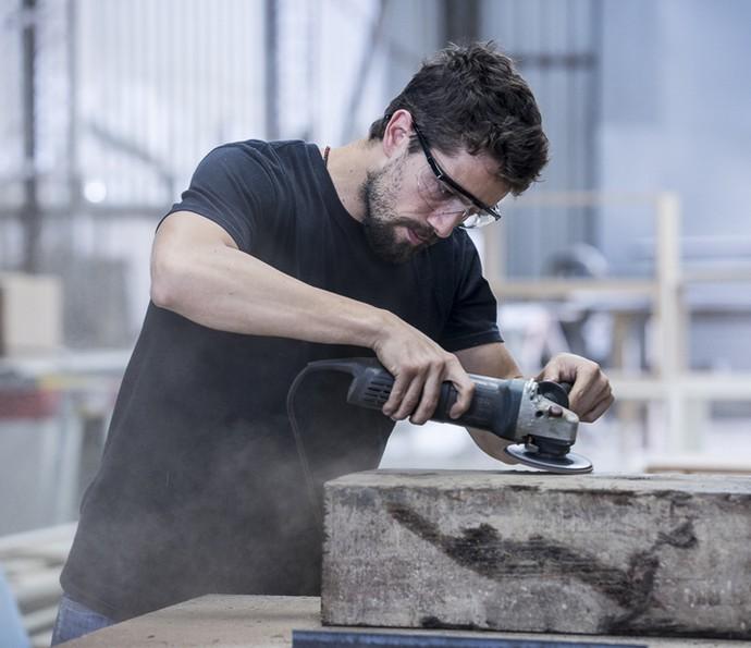 Rafael lixa peça em madeira (Foto: Ellen Soares/Gshow)