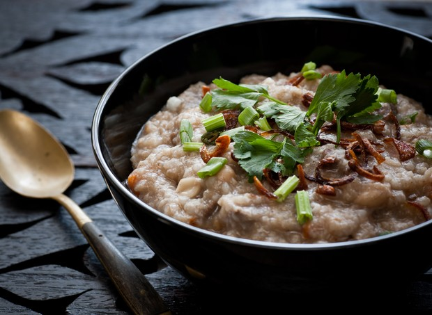 traditional homemade Bubur Lambuk congee in black bowl on wooden carving top (Foto: Getty Images/iStockphoto)