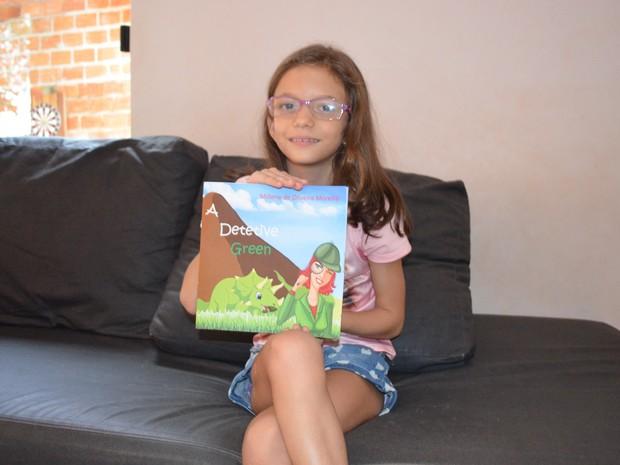 Millene exibe com orgulho seu primeiro livro (Foto: Rogério Aderbal/G1)