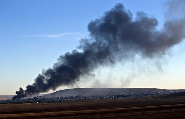 Fumaça é vista em região controlada pelo grupo radical Estado Islâmico em Kobani, após bombardeios da coalizão internacional neste sábado (8) (Foto: Vadim Ghirda/AP)