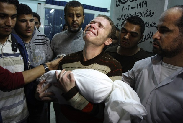 O palestisno Jihad Masharawi chora a morte do filho Ahmad, de 11 meses, no hospital de Shifa, após ataque israelense à Cidede de Gaza na quarta-feira (14) (Foto: Majed Hamdan/AP)