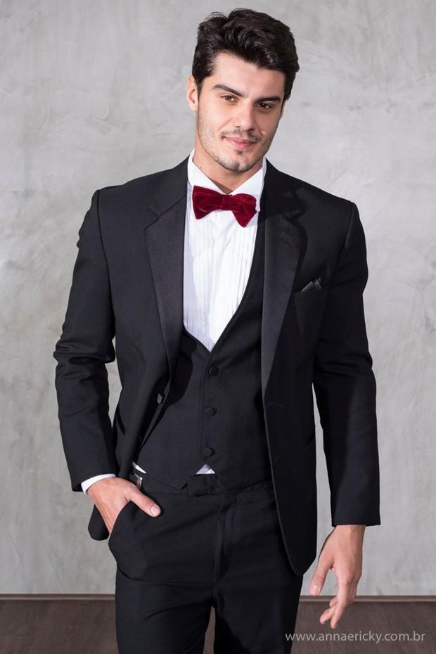 Para começar a ousar, mesmo que seja num pequeno detalhe, dê cor à sua gravata. O vermelho, por exemplo, revela um contraste interessante com o restante do traje em preto. (Foto: Annaericky)