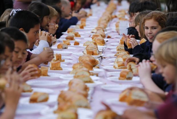 Crianças 'devoram' sanduíche de 16 m de comprimento durante o Dia Nacional da Manteiga de Amendoim e Geleia nos EUA (Foto: Mike Blake/Reuters)