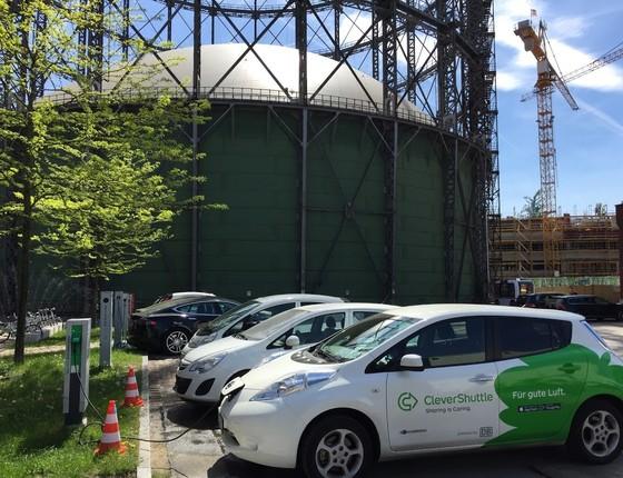 Carros elétricos são recarregados no campus Euref, em Berlim, Alermanha. Ao fundo, a antiga estrutura de um gasômetro, hoje desativada (Foto: Bruno Calixto/ÉPOCA)