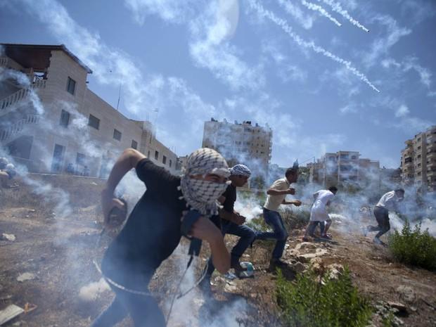 Palestinos correm para se proteger em meio a bombas de gás lacrimogêneo atirada por soldados israelenses durante protesto contra a ofensiva na Faixa de Gaza, perto da prisão militar israelense de Ofer, na região de Ramallah, Cisjordânia (Foto: Majdi Mohammed/AP)