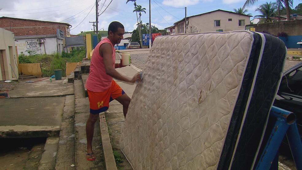 Morador de Rio Formoso, Ivan José da Silva tenta reutilizar pertences encontrados na lama (Foto: Reprodução/TV Globo)