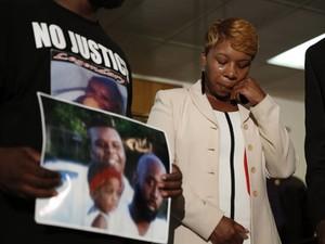 Lesley McSpadden, mãe do adolescente morto Michael Brown, chora ao olhar para a foto da família carregada pelo pai de Michael (Foto: Jeff Roberson/AP)