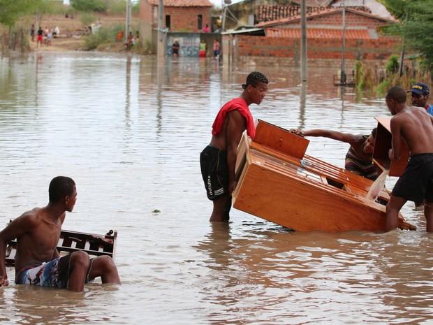 Moradores retiram móveis de casas após rio transbordar (Foto: Divulgação/prefeitura de Riachão do Jacuípe)