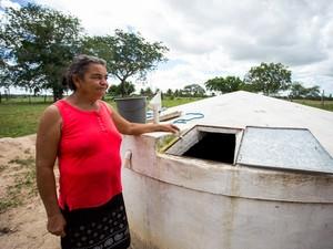 Agricultora mostra cisterna que só enche com a água da chuva, já que não é cadastrada para abastecimento. (Foto: Jonathan Lins/G1)