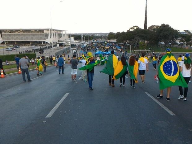 Manifestantes enrolados em bandeiras do Brasil seguem em direção ao Palácio do Planalto para participar de protesto contra o governo da presidente Dilma Rousseff (Foto: Alexandre Bastos/G1)