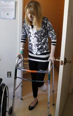 Adrianne Haslet utiliza andador para voltar para a cama em hospital em Boston (Foto: AP Photo/Bizuayehu Tesfaye)