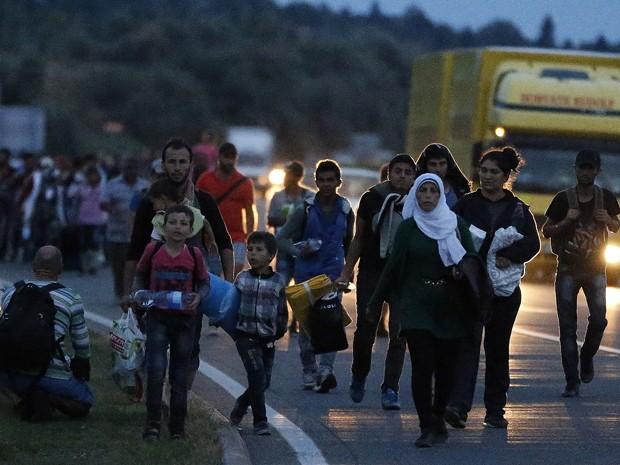 Imigrantes caminham em estrada perto de Budapeste, na Hungria, em direção à fronteira com a Áustria, na sexta (4) (Foto: AP Photo/Frank Augstein)