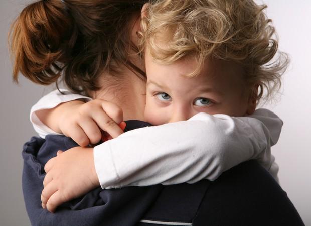 Criança triste no colo da mãe (Foto: Shutterstock)