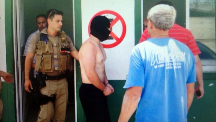 Policial suspeito do crime usa capuz preto e é detido  (Foto: Guto Kuerten/Agência RBS)