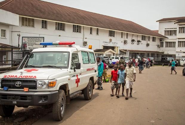 Neste domingo (14), garotos passam ao lado de ambulância equipada para carregar pacientes de ebola em Freetown, Serra Leoa; população terá de ficar fechada em casa por três dias a partir desta sexta-feira (Foto: AP Photo/Michael Duff)