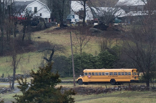 Ônibus escolar passa por rua para recolher alunos em Newtown. Escolas voltaram a ter aulas nesta terça-feira (18) (Foto: AFP)