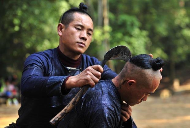 Em 2011, um homem foi fotografado usando uma foice para raspar o cabelo de outro morador da minoria étnica Miao na aldeia de Basha, na província chinesa de Guizhou (Foto: Sheng Li/Reuters)