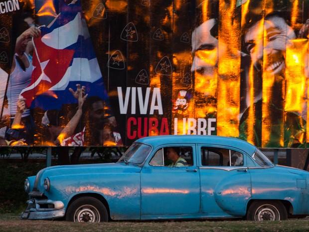 Taxista em automóvel americano percorre rua de Havana, em Cuba, na segunda-feira (14) (Foto: Desmond Boylan/AP)