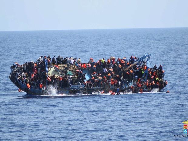 Imigrantes pulam de um barco durante naufrágio antes da chegada do resgate pelos navios 'Bettica' e 'Bergamini' da marinha italiana na costa da Líbia  (Foto: Marinha italiana/Divulgação via Reuters)