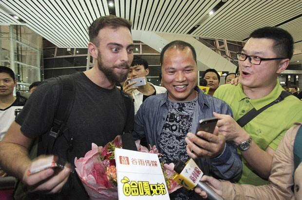 Matt Stopera é recebido pelo 'irmão laranja' no aeroporto da China (Foto: Reuters)