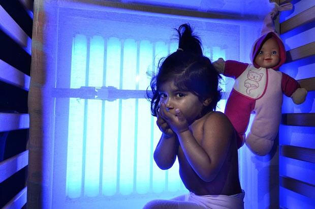 A inglesa Areesha, que passa 12 horas por dia em cama com paineis que emitem raios UV em tratamento contra síndrome rara. (Foto: Caters)