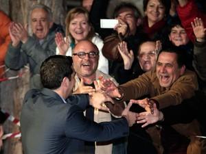 Alexis Tsipras, líder do partido Syriza, cumprimenta seus apoiadores do lado de fora da sede do partido em Atenas, neste domingo (25) (Foto:  AP Photo/Lefteris Pitarakis)