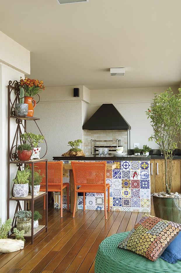 Com 34 m², que representam metade da área social no apartamento de 174 m², a varanda é o local mais importante para os moradores. Em frente à churrasqueira e à pia, a decoradora Aline Oishi criou a bancada com azulejos antigos (Foto: Marcelo Magnani e Maíra Acayaba/Casa e Jardim)