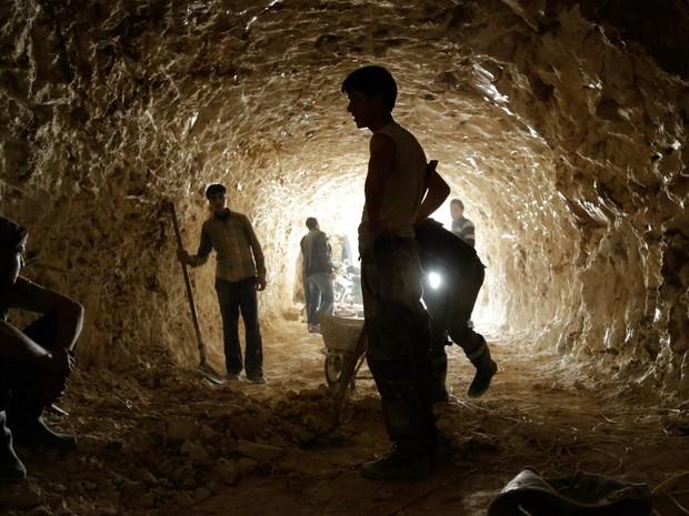 Combatentes rebeldes cavam um túnel nas montanhas para ser usado como abrigo dos bombardeios de forças leais ao presidente Bashar al-Assad em al-Latamna, no norte da Síria (Foto: Khalil Ashawi/Reuters)