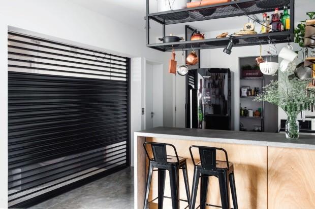 Distribuição. Um portão de aço com acionamento automático, da Tecnoportas, pode isolar o quarto. Na cozinha, a geladeira fica ao lado do vão que dá na despensa (Foto: Maíra Acayaba / Editora Globo)