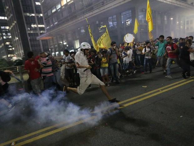 Manifestante se prepara para chutar bomba arremessada pela PM.  (Foto: Daniel Teixeira/Estadão Conteúdo)