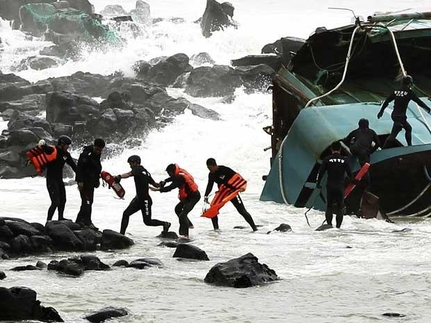 Socorristas resgatam pescador chinês de um dos barcos virados pela força do tufão 'Bolaven'. (Foto: Kang Jae-nam / Newsis / AP Photo)
