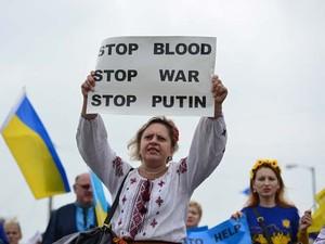 Mulher segura cartaz de protesto contra o conflito na Ucrânia durante cúpula da Otan em Newport, no País de Gales (Foto: AFP PHOTO / CARL COURT)