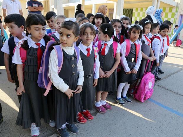 Crianças fazem fila para entrada na escola em Bagdá (Foto: Karim Kadim/AP)